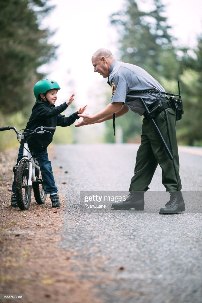 Police Officer Talking to Child on Bike : Stock Photo