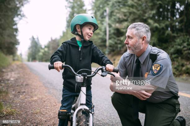 police officer talking to child on bike - forze di polizia foto e immagini stock
