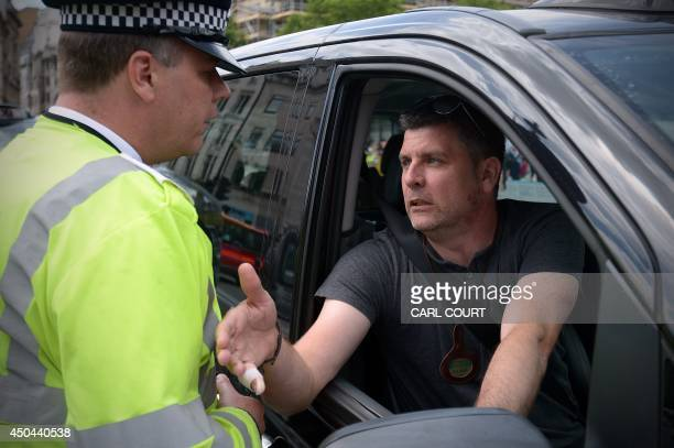 A police officer talks a London black cab driver during a protest against a new private taxi service 'Uber' a mobile phone app in central London on...