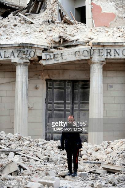 Police officer talks on a mobile phone, April 6, 2009 in front of a damaged building in the center of the Abruzzo capital L'Aquila, the epicenter of...