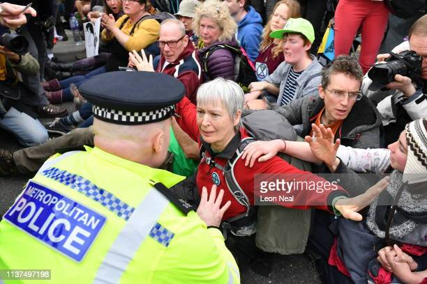 A police officer talks to a protester as they remove people from a blockade on Waterloo Bridge during the second day of a coordinated protest by the...