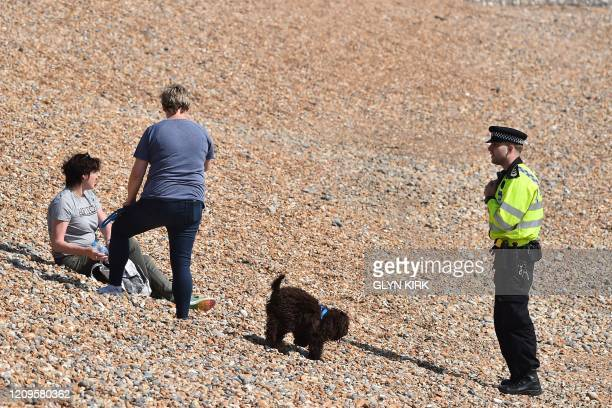A police officer talks to people sitting on the beach in Brighton on the south coast of England on April 10 2020 as warm weather tests the nationwide...