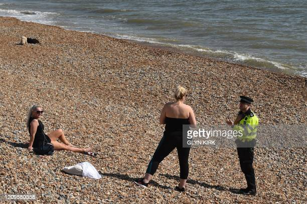 A police officer talks to people sitting on the beach in Hove on the south coast of England on April 10 2020 as warm weather tests the nationwide...