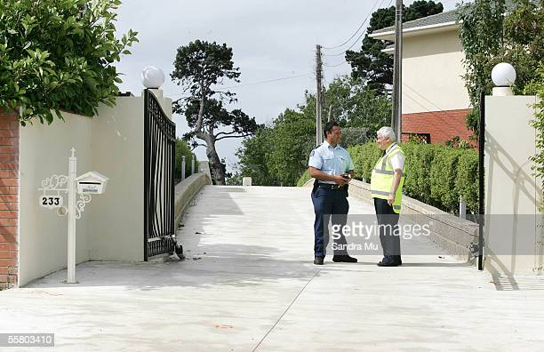 Police Officer talks to the security guard manning the entrance to the property in Howick Auckland Monday 7th March 2005 where 42 year old Qing Zhao...
