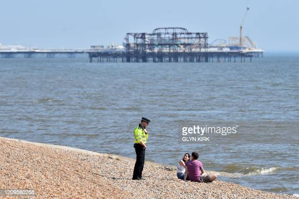 A police officer talks with a couple sitting on the beach in Hove on the south coast of England on April 10 2020 as warm weather tests the nationwide...