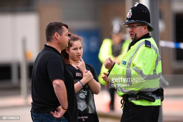 TOPSHOT A police officer talks with a man and a girl wearing a Tshirt of US singer Ariana Grande branded for the concert at the Manchester Arena in...