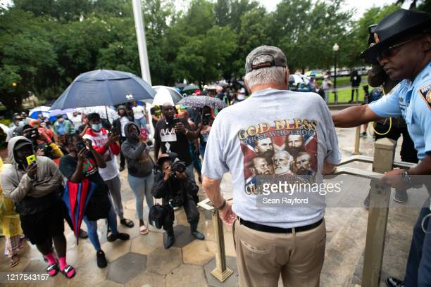 A police officer talks with a man who identified himself as Jose Hermanse wearing a shirt displaying Civil War Confederate generals as demonstrators...