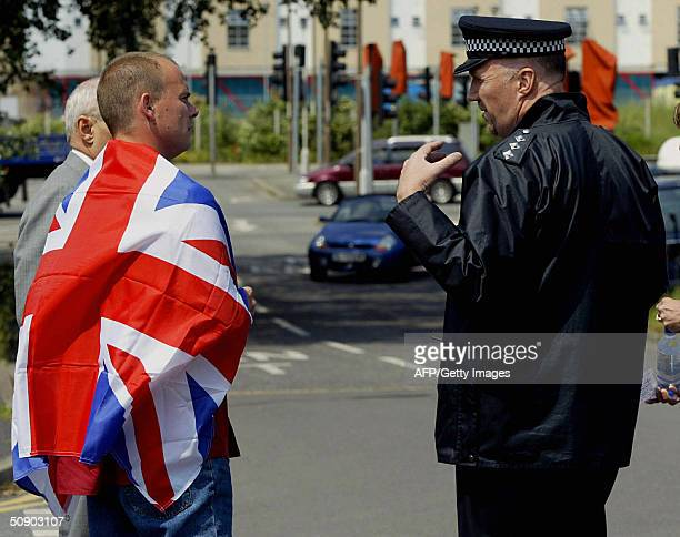 A police officer talks with a man with the Union jack flag on his shoulder outside Belmarsh magistrate court in London 27 May 2004 before the police...
