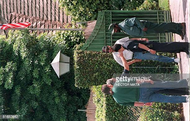 A police officer talks with members of the Bekins moving company hired by the Los Angeles County Sheriff's Department in front of OJ Simpson's house...