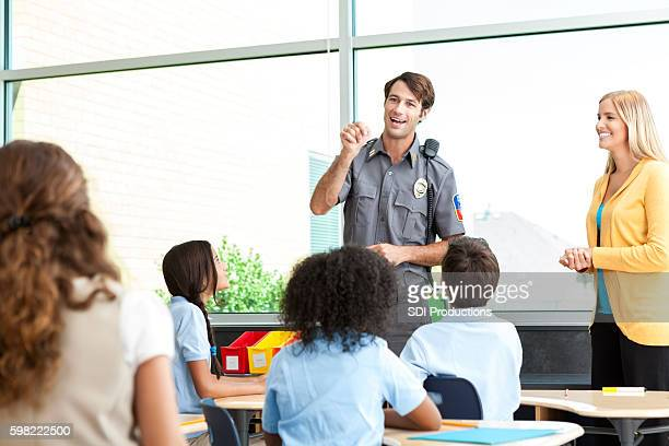 Police officer teaches class of children about safety.