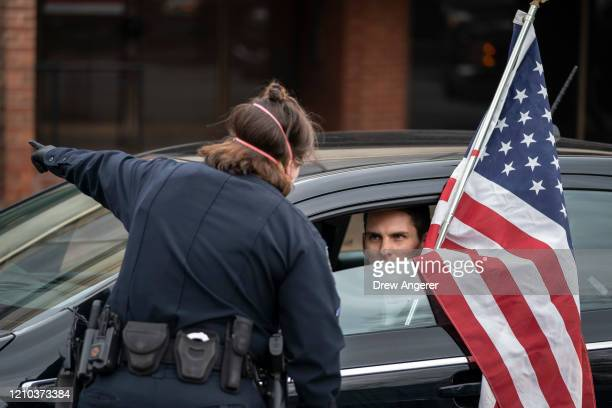 A police officer tells a protester with the group Reopen Maryland that his vehicle needs to move as they rally near the State House to call on the...