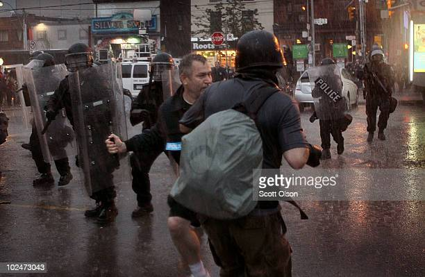 A police officer threatens to punch a photographer taking pictures of a journalist being arrested at the G20 summits June 27 2010 in Toronto Canada...