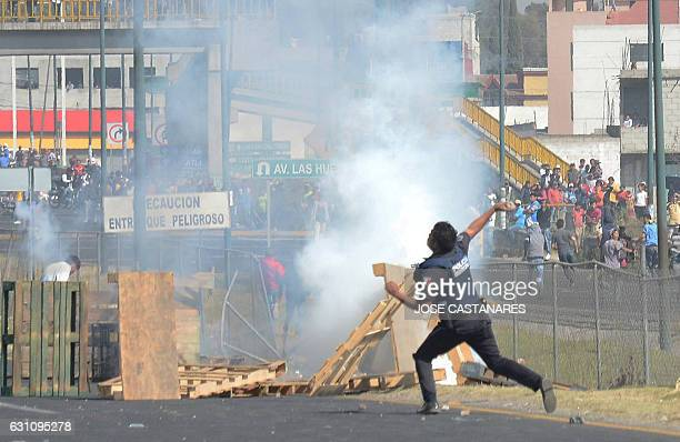 TOPSHOT A police officer throws a stone at demonstrators protesting against the rise of fuel prices in Puebla Mexico on January 6 2017 The death toll...