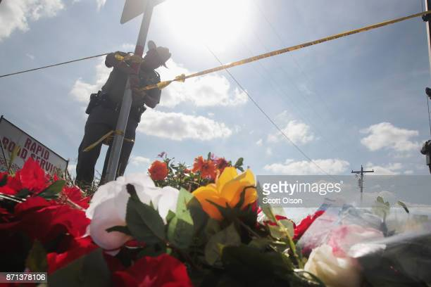A police officer ties off crime scene tape near a small memorial close to the First Baptist Church of Sutherland Springs on November 7 2017 in...