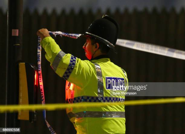 A police officer ties police crime scene tape close to the Manchester Arena on May 23 2017 in Manchester England An explosion occurred at Manchester...