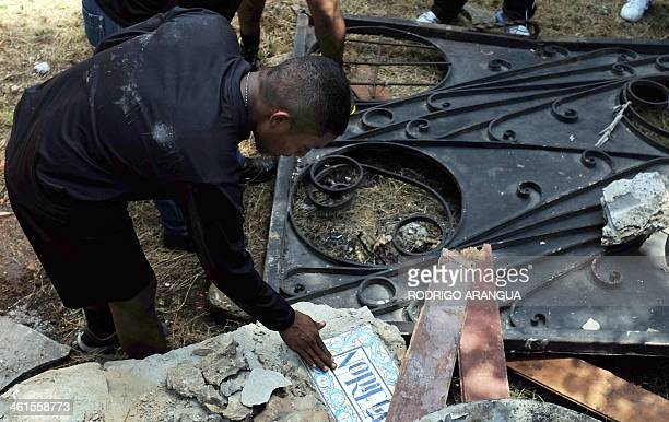 A police officer touches tiles with the name 'Noriega' at the residence of Panama's former dictador Manuel Antonio Noriega currently imprisoned in...