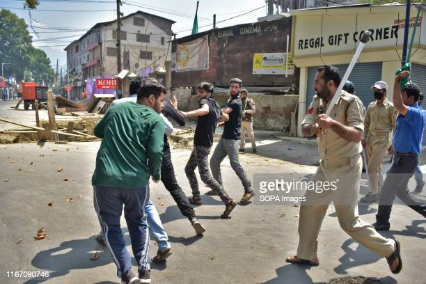 A police officer tries striking Kashmir Shiite mourners during the procession Authorities in parts of Srinagar imposed strict restrictions to prevent...