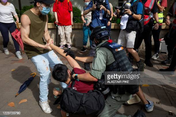 Police officer tries to detain a man during a rally against a new national security law in Hong Kong on July 1 on the 23rd anniversary of the city's...