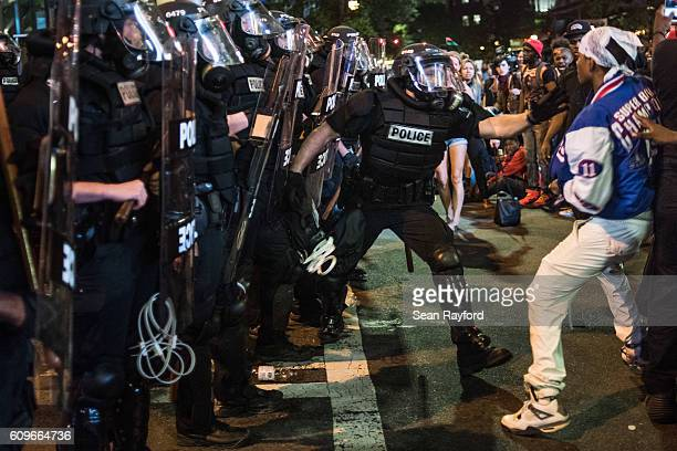 A police officer tries to grab a demonstrator during protests September 21 2016 in downtown Charlotte NC The North Carolina governor has declared a...