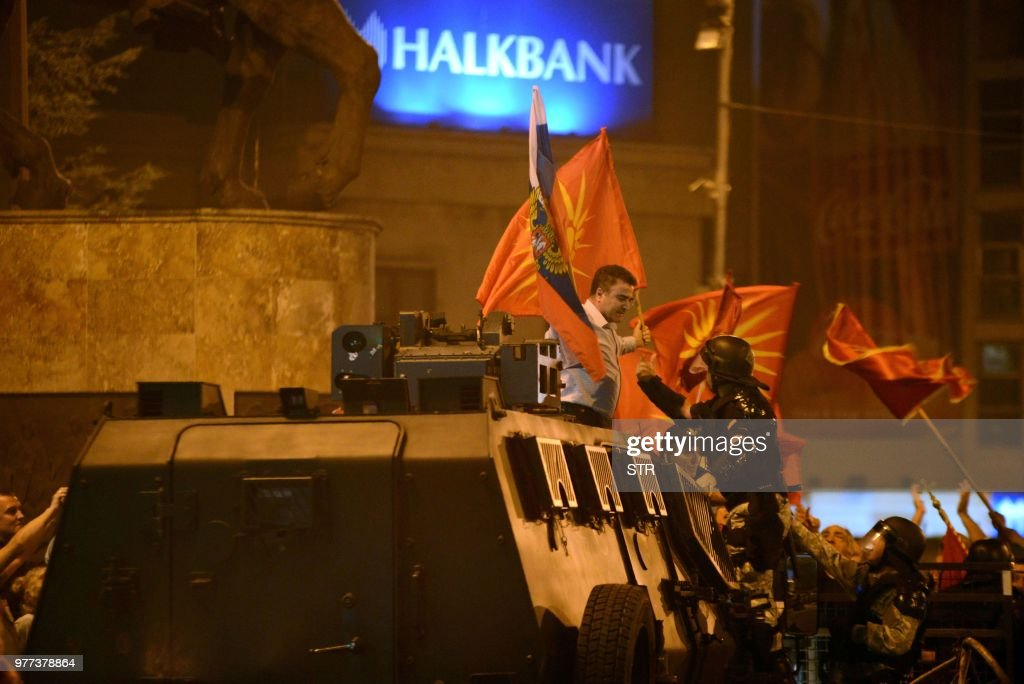 A police officer tries to grab a protester waving former Macedonian and Russian flags atop an armoured police vehicle during a protest of opponents of the preliminary agreement between Macedonia and Greece to rename the nation the Republic of North Macedonia, in front of the Parliament in Skopje on June 17, 2018. - Greece and Macedonia on June 17 signed a historic preliminary agreement to rename the small Balkan nation the Republic of North Macedonia, ending a row that has poisoned relations between the two neighbours since 1991.