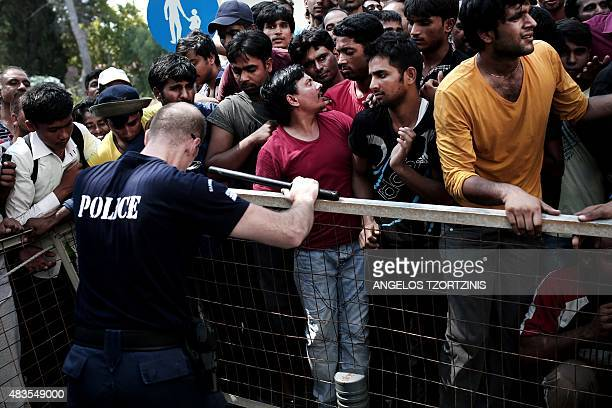 A police officer tries to push back migrants waiting behind a fence to be registered by the police outside a police station on the island of Kos on...