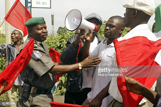 A police officer tries to stop protesting workers from marching into the town 11 October 2004 during a protest rally by the Nigeria Labour Congress...