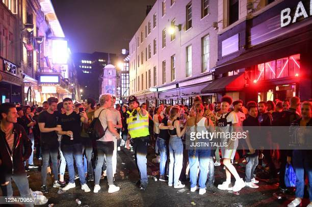 A police officer tries to tell revellers filling the street outside bars in the Soho area of London on July 4 that the road has been reopened to car...