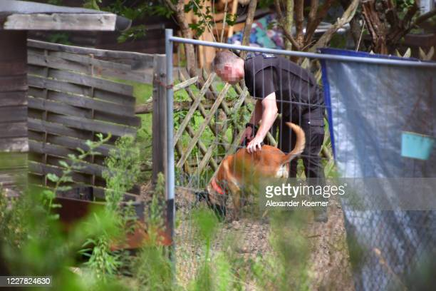 Police officer uses a detection dog while digging at an allotment as police continue to search the area in relation to the disappearance of Madeleine...