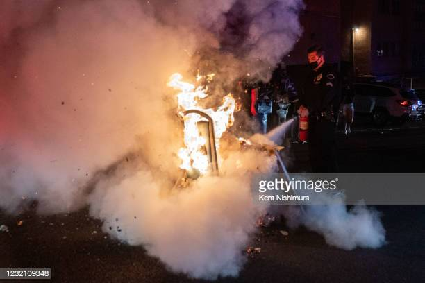 Police Officer uses a fire extinguisher on a small fire that was set in the middle of Roebling Ave. As UCLA Students take to the street reacting to...