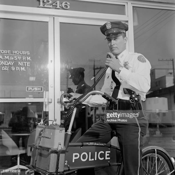 A police officer uses a Motorola radio on a Schwinn police bicycle in St Petersburg Florida circa 1955