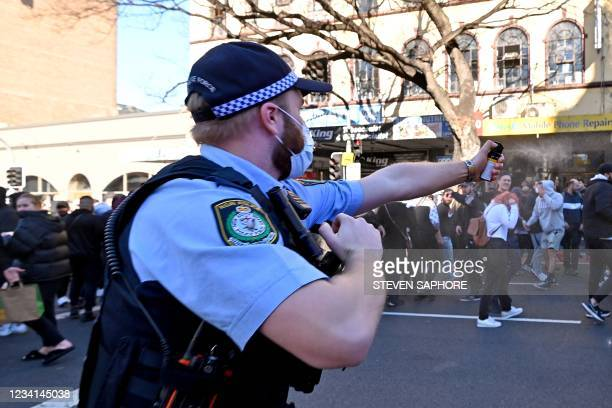 Police officer uses a spray to disperse protesters during an anti-lockdown rally in Sydney on July 24 as thousands of people gathered to demonstrate...