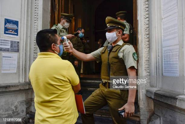 Police officer uses a thermometer to measure the temperature of a citizen at police station, before the metropolitan area of Santiago enters in a...