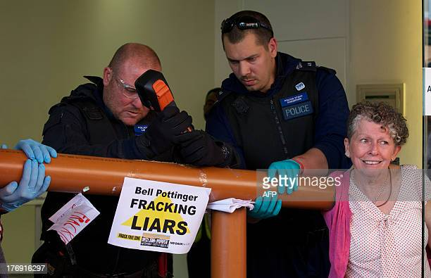 A police officer uses a tool to cut through a pipe glued to the arm of a protester forming a makeshift barrier as climate protesters block the...