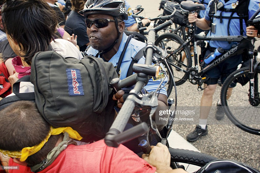 A police officer uses his bicycle to push back activists that were trying to prevent a delegate bus from reaching the convention center.