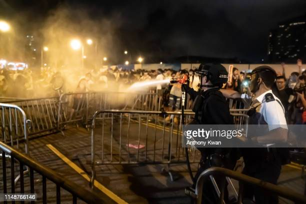 A police officer uses pepper spray during a clash at Legislative Council after a rally against the extradition law proposal at the Central Government...