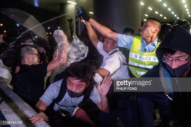 A police officer uses pepper spray during a clash at Legislative Council in Hong Kong after a rally against a controversial extradition law proposal...