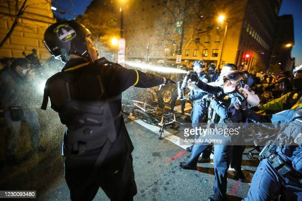 """Police officer uses pepper spray to disperse clashing groups of protesters during the """"Million MAGA March"""" from Freedom Plaza to the US Capitol in..."""