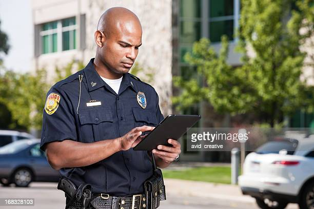 police officer using computer tablet - police force stock pictures, royalty-free photos & images