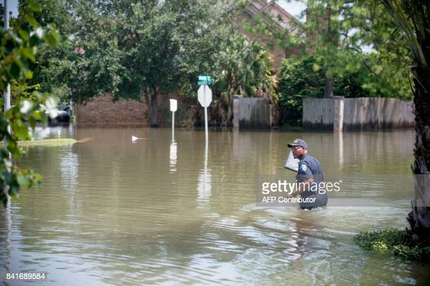A police officer walks across a flooded street in Port Arthur Texas September 1 2017 Stormweary residents of Houston and other Texas cities began...