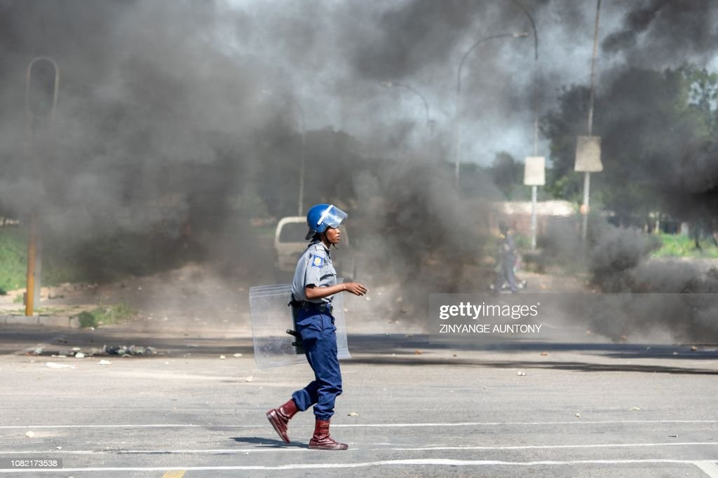 A police officer walks amid smoke during a