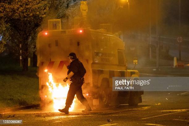 Police officer walks behind a police vehicle with flames leaping up the rear after violence broke out in Newtownabbey, north of Belfast, in Northern...
