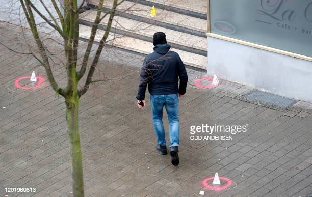 A police officer walks in front of one of the bar targeted in a shooting at the Heumarkt in the centre of Hanau near Frankfurt am Main western...