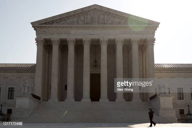 """A police officer walks in front of the US Supreme Court April 6 2020 in Washington DC The Supreme Court has announced that it """"will postpone the oral..."""