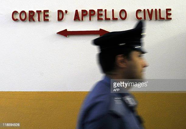 A police officer walks inside the Milan court house on July 9 2011 A Milan court ordered Italian premier Silvio Berlusconi's Fininvest company today...