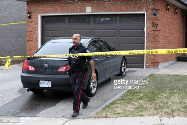 A police officer walks inside the police tape at Alek Minassian's house in Richmond Hill Ontario on April 24 2018 A van driver who ran over 10 people...