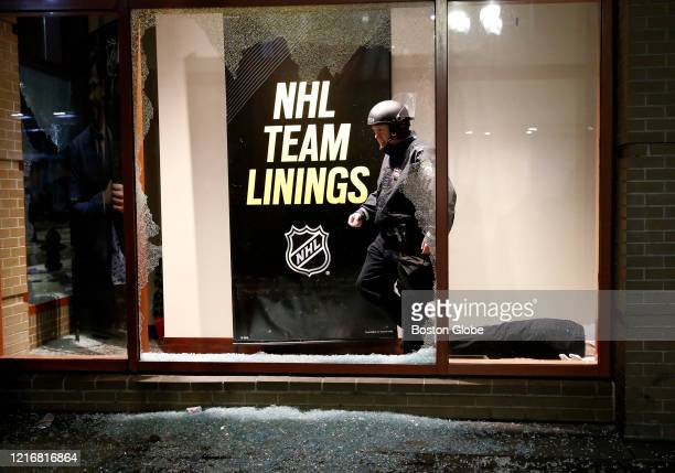 A police officer walks out of an NHL store in Downtown Crossing after the windows were smashed following a march to protest the death of George Floyd...