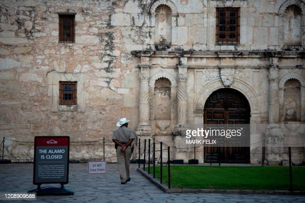A police officer walks outside of the closed Alamo on April 1 2020 in downtown San Antonio Texas during a stay at home order amid the novel...