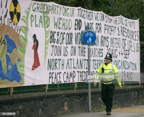 A police officer walks past a banner erected on the gates of Tredegar Park where protestors have set up a peace camp close to the Celtic Manor Resort...