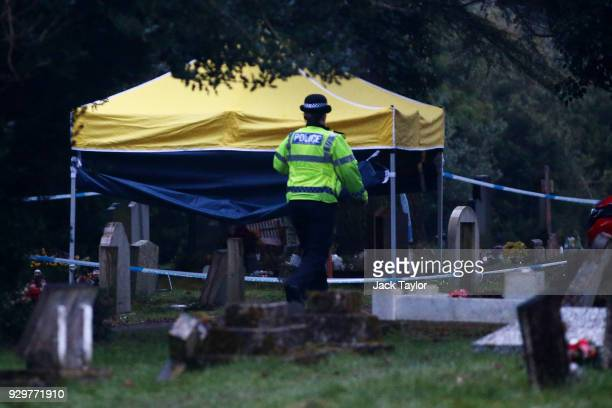 A police officer walks past a forensics tent over the grave of former Russian double agent Sergei Skripal's wife Lyudmila in London Road cemetery on...