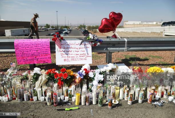 A police officer walks past a makeshift memorial outside Walmart near the scene of a mass shooting which left at least 22 people dead on August 5...